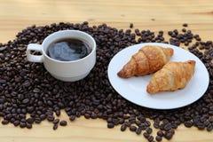 一个杯子热的咖啡和在烤豆新月形面包有bokeh背景 免版税图库摄影