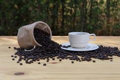 一个杯子热的咖啡和烤咖啡豆在一个袋子有bokeh背景 免版税库存照片