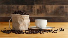 一个杯子热的咖啡用在温暖的光的烤咖啡豆有木背景 免版税库存照片