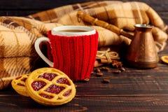 一个杯子热的咖啡,在一个被编织的盖子和自创曲奇饼,Cezve和香料,在一张木桌上说谎在方格的格子花呢披肩附近 库存图片