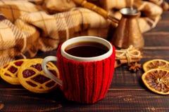 一个杯子热的咖啡,在一个被编织的盖子和自创曲奇饼,Cezve和香料,在一张木桌上说谎在方格的格子花呢披肩附近 库存照片