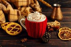 一个杯子热的咖啡,在一个被编织的盖子和自创曲奇饼,Cezve和香料,在一张木桌上说谎在方格的格子花呢披肩附近 免版税库存照片