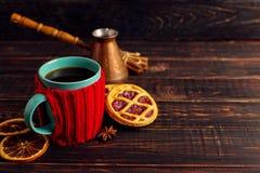 一个杯子热的咖啡,在一个被编织的盖子和自创曲奇饼,Cezve和香料,在一张木桌上说谎 库存照片