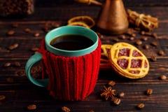 一个杯子热的咖啡,在一个被编织的盖子和自创曲奇饼,Cezve和香料,在一张木桌上说谎 免版税库存照片