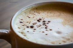 一个杯子热的拿铁,在木桌上的咖啡艺术在relex时间 图库摄影