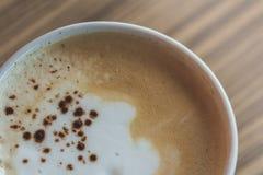 一个杯子热的拿铁,在木桌上的咖啡艺术在relex时间 免版税库存图片