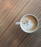 一个杯子热的拿铁,在木桌上的咖啡艺术在relex时间 库存图片