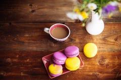 一个杯子热的无奶咖啡和明亮的蛋白杏仁饼干在一张木桌上在黑暗的背景与五颜六色的bokeh 库存照片