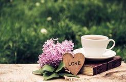 一个杯子热的茶、一本书和丁香反对绿草背景  浪漫概念 葡萄酒设色 复制空间 免版税库存照片