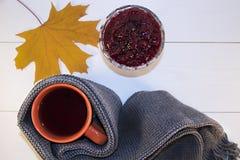 一个杯子热的茶用在白色背景的一条围巾包裹的山莓果酱 免版税库存图片