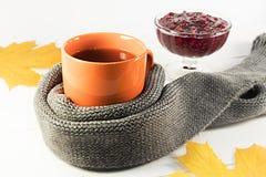 一个杯子热的茶用在白色背景的一条围巾包裹的山莓果酱 免版税库存照片