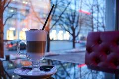 一个杯子热,褐色鲜美热奶咖啡用在茶碟的牛奶划分了成与秸杆的层数在一个咖啡馆的桌上在晚上 库存照片