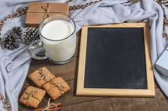 一个杯子牛奶、肉桂条、自创饼干和板岩在圣诞节装饰 库存照片