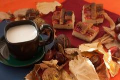 一个杯子牛奶咖啡、自创饼几个片断用果酱,栗子和干燥秋叶红色表面上 免版税图库摄影
