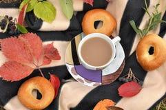 一个杯子牛奶茶、甜新鲜的小圆面包和五颜六色的秋叶在一条镶边温暖的野餐毯子 免版税库存图片