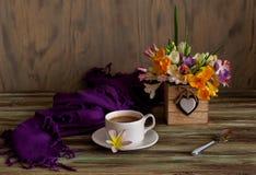一个杯子用早晨咖啡和花小苍兰花束  库存照片