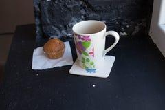 一个杯子用茶和杯形蛋糕在窗口附近 库存照片
