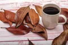 一个杯子的大角度看法与秋叶的咖啡在土气 库存图片