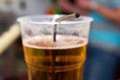 一个杯子的特写镜头与秸杆的啤酒 免版税库存图片