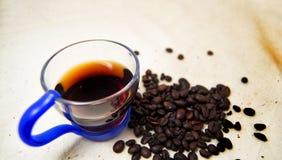 一个杯子的软的焦点精力充沛的饮料注入和咖啡豆有未加工的背景 对戒毒所和健康概念 免版税图库摄影