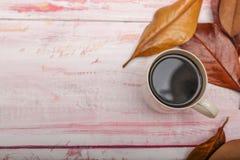 一个杯子的顶视图与秋叶的咖啡在土气木 免版税图库摄影