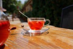一个杯子红色茶 绿茶用在桌上的草莓 在被弄脏的街道背景的莓果茶 街道咖啡馆概念 库存照片
