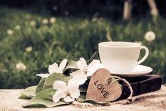 一个杯子红茶、书和一棵开花的苹果树的分支 苹果计算机开花、心脏和芬芳茶 葡萄酒设色 库存图片