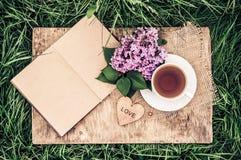 一个杯子红茶和与空白页的一本开放日志在绿草 浪漫概念 与心脏的木卡片 葡萄酒设色 免版税库存照片