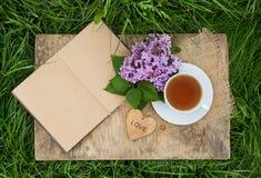 一个杯子红茶和与空白页的一本开放日志在绿草 浪漫概念 与心脏的木卡片 库存照片