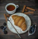 一个杯子红茶用一个新鲜的金黄新月形面包和莓果 在一个木背景 新鲜的面包店 免版税库存图片