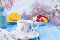 一个杯子芬芳早晨咖啡,果子冰淇凌和和花是白色和桃红色在蓝色木背景 抽象背景同类的照片结构葡萄酒 库存图片