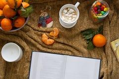 一个杯子芳香咖啡用蛋白软糖,成熟普通话,与干净的白色板料的一本书,圣诞节的一个蜡烛 免版税库存照片
