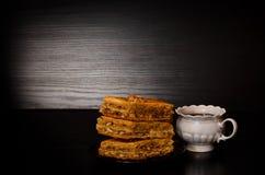 一个杯子茶和土耳其果仁蜜酥饼蜂蜜板材  复制空间,黑背景 库存图片