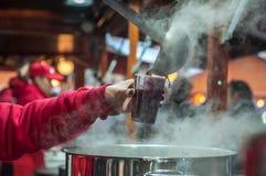 给一个杯子被仔细考虑的酒的妇女特写镜头在圣诞节市场上 图库摄影