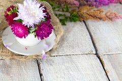 一个杯子装饰内部室桃红色美丽的花的花在白色桌背景 库存图片