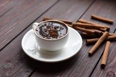 一个杯子黑暗的木表面上的热巧克力装饰用肉桂条 免版税图库摄影