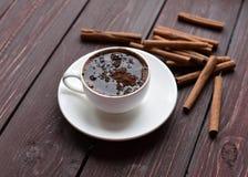 一个杯子黑暗的木表面上的热巧克力装饰用肉桂条 库存图片