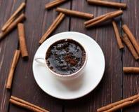 一个杯子黑暗的木表面上的热巧克力装饰用肉桂条 库存照片