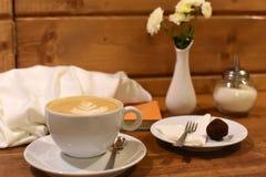 一个杯子cappucino、一本书、一条围巾和一个花瓶有秋天的在葡萄酒咖啡馆的一张黑暗的木桌上开花 库存图片