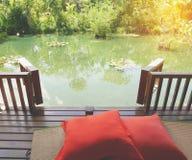 一个松弛绿色池塘的木露台有竹席子和枕头的 库存图片