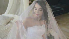 一个柔和的可爱的浅黑肤色的男人的早晨 美丽的新娘是微笑和看接触面纱的窗口 股票视频