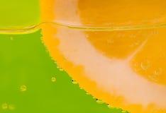 一个柠檬的细节在一块玻璃的在绿色背景 库存照片