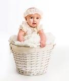 一个柳条筐的逗人喜爱的小女孩 免版税库存图片