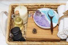 一个柳条筐的部分与一个集合的温泉做法、五颜六色的盐、芳香油、石头、一个蜡烛和软的毛巾的 免版税库存照片