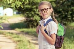 一个校服的微笑的年轻小学生反对树  免版税库存图片