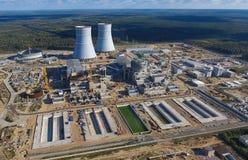 一个核电站的航测建设中 能源厂的设施和建筑 可更新的绿色能量的概念:一棵雏菊和草在残破的核能的标志 库存图片