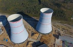 一个核电站的航测建设中 能源厂的设施和建筑 可更新的绿色能量的概念:一棵雏菊和草在残破的核能的标志 免版税库存照片