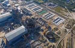 一个核电站的航测建设中 能源厂的设施和建筑 可更新的绿色能量的概念:一棵雏菊和草在残破的核能的标志 免版税图库摄影