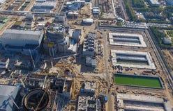 一个核电站的航测建设中 能源厂的设施和建筑 可更新的绿色能量的概念:一棵雏菊和草在残破的核能的标志 库存照片