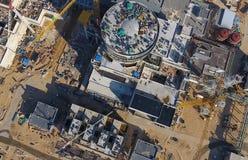一个核电站的航测建设中 能源厂的设施和建筑 可更新的绿色能量的概念:一棵雏菊和草在残破的核能的标志 免版税库存图片